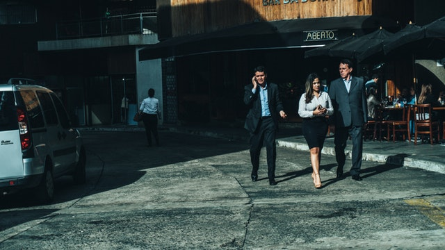 A photograph of three people walking dressed in business attire